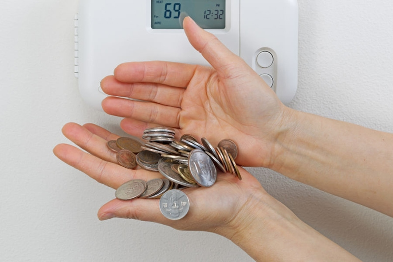 Hand holding quarters next to thermostat, 5 Ways to Save Money on Your Air Conditioning & Summer Energy Bill