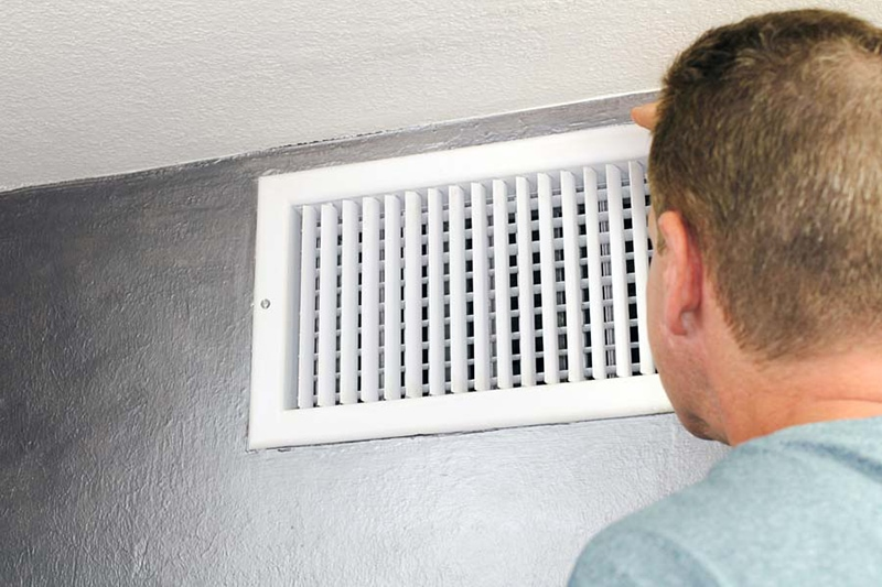 man in light blue shirt looking at air vent on wall