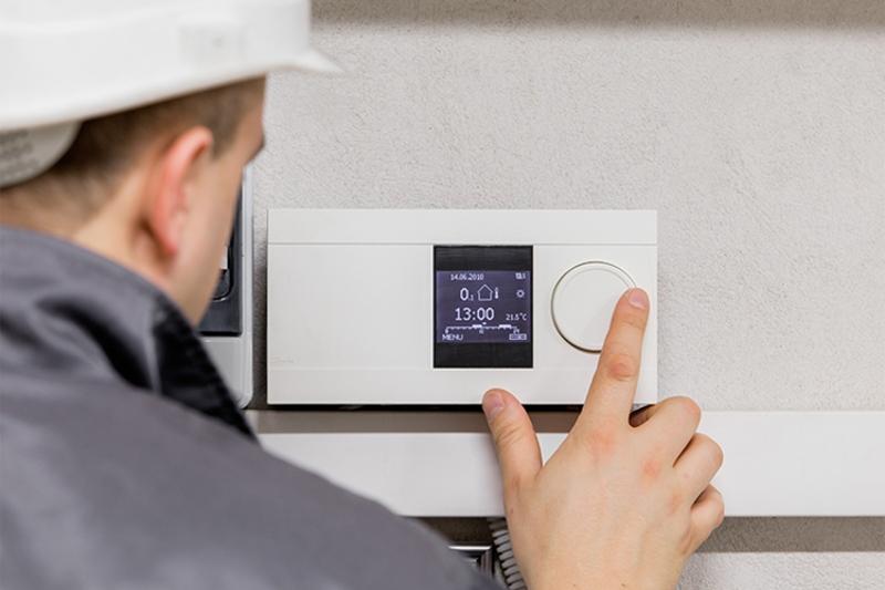 HVAC Tech adjusting thermostat