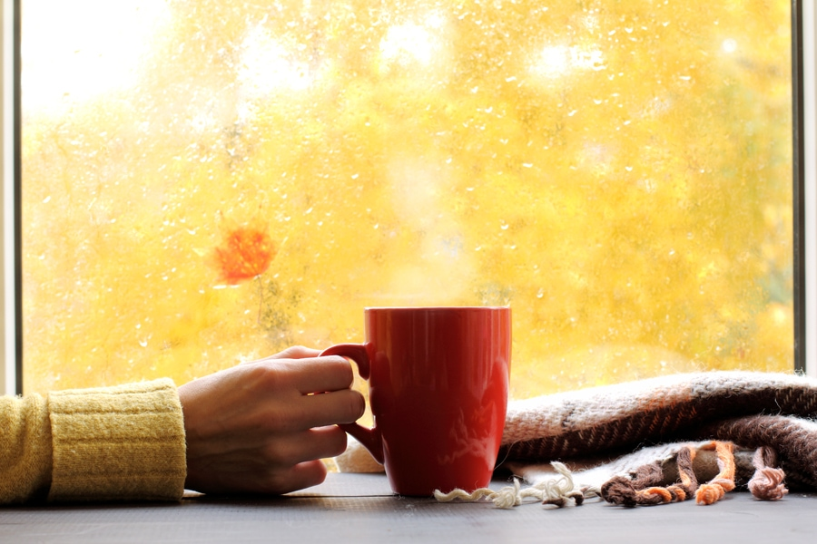red mug of hot drink, when behind a window is rain in autumn in San Jose, CA
