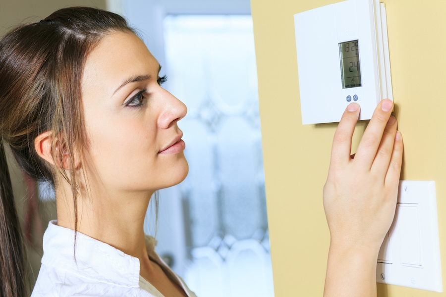Woman adjusting a home thermostat, Why Is My Air Conditioner Blowing Hot Air? | HVAC, Maintenance